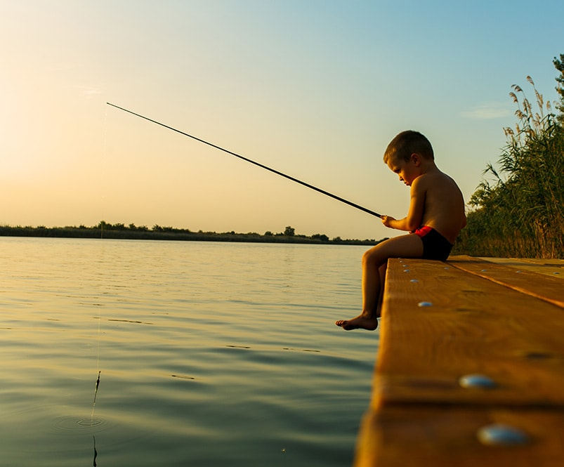 boy with a fishing pole at sunset