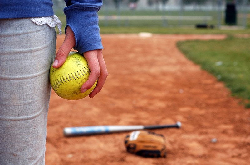 girl holding yellow softball at her hip